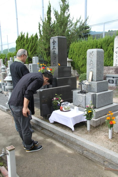My 24 year old son bows deeply in front of the family crypt holding the ashes of Suetaro who was killed at 24 years of age.