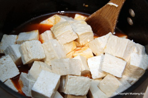 Carefully add tofu to braising sauce