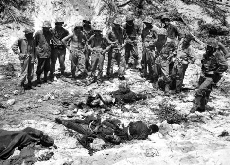 U.S. Marines inspect the bodies of three Japanese soldiers killed in the invasion at Peleliu island at the Palau group, September 16, 1944. (AP Photo/Joe Rosenthal)